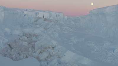 Survol des terres glacées sous un ciel rosé et le soleil bas de l'été austral