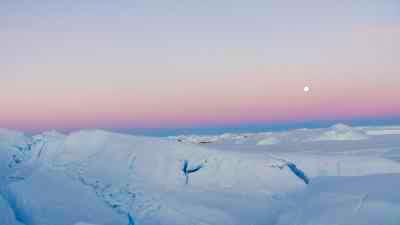 Chaos de glaces du glacier l'Astrolabe, sous un ciel rosé et le soleil bas de l'été austral