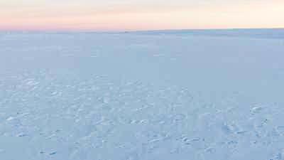 Survol des terres glacées sous un ciel rosé et le soleil rasant de l'été austral