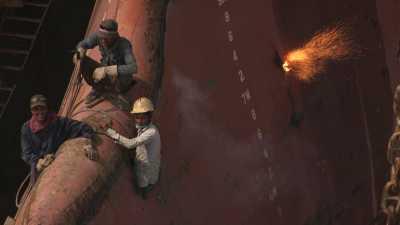 Gros plans d'ouvriers démantelant des bateaux