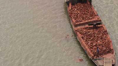 Hommes travaillant sur l'eau, mise en tas de briques en bord de plage