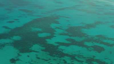 Survol d'un atoll en longueur, navire abandonné
