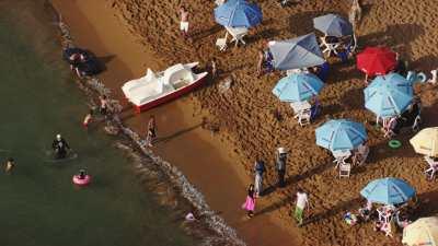 Petite plage, baigneurs et parasols colorés