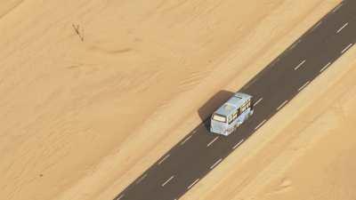 Autocar bariolé sur la route saharienne
