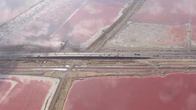 Une autoroute traverse les marais salants roses du lac Mariout