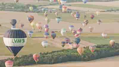 Envol de montgolfières au-dessus des champs