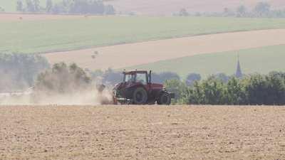 Tracteur qui laboure aux abords d'un village de campagne