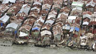 L'environnement misérable de la Cité Soleil, masures aux toits de tôle et barques