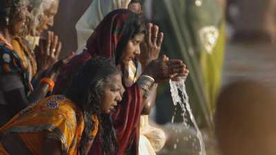 Femmes et Sadhu se baignant lors de la Kumbh Mela