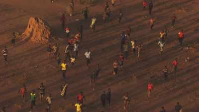 Hommes et enfants accourant au son d'un hélicoptère