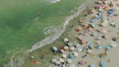 Gros plans sur la plage Martil et ses nombreux baigneurs, les parasols, les pédalos