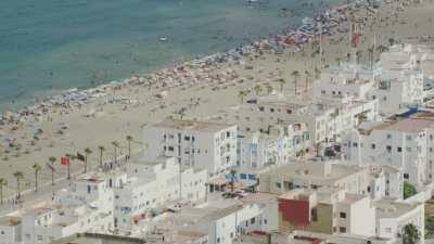 Gros plans sur la plage Martil et Miramar, les nombreux baigneurs, les parasols, les pédalos