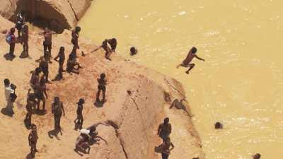 Jeux d'enfants dans les eaux jaunes de la rivière