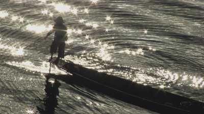 Pêcheur en pirogues en contre-jour