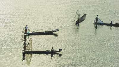 Pêcheurs sur les pirogues, en contre-jour