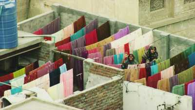 Des femmes font sécher la lessive colorée sur les toits de la ville