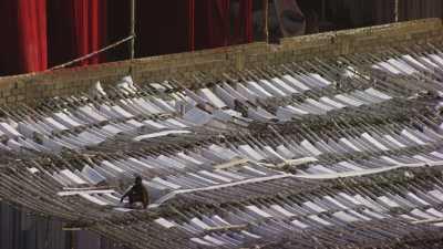 Zoom sur des ouvriers étendant les textiles dans une usine près de Karachi