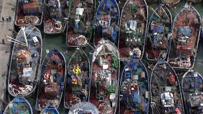 Survol du petit port de pêche, de la ville, d'une plage